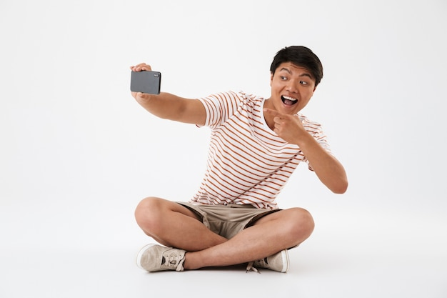 Portrait of a cheerful young asian man taking Premium Photo