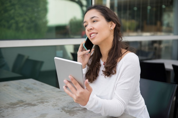 Portrait of cheerful young businesswoman talking on mobile phone Free Photo