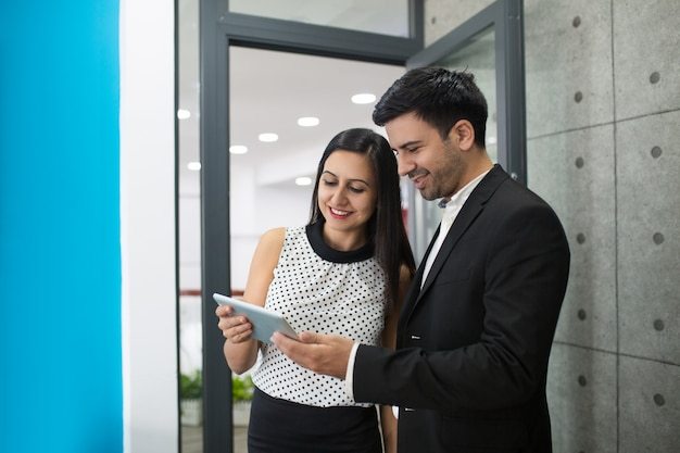 Portrait of cheerful young colleagues browsing on digital tablet Free Photo
