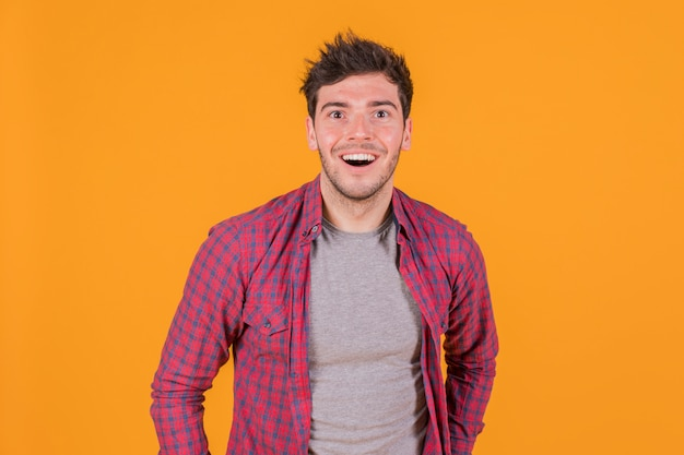 Portrait of a cheerful young man against an orange background Free Photo