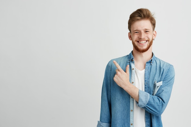 Portrait of cheerful young man smiling pointing finger up. Free Photo