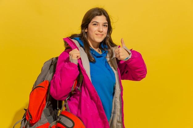 Ritratto di una ragazza allegra giovane turista con borsa e binocolo isolato sulla parete gialla dello studio Foto Gratuite