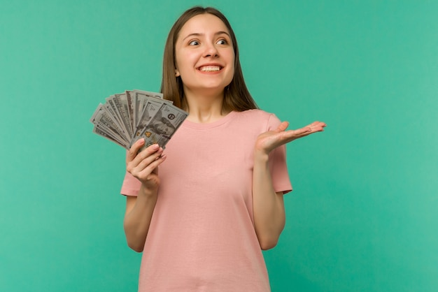 Portrait of a cheerful young woman holding money banknotes and celebrating isolated on blue background Premium Photo