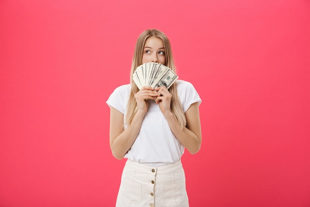 Portrait of a cheerful young woman holding money banknotes and celebrating isolated over pink background Premium Photo