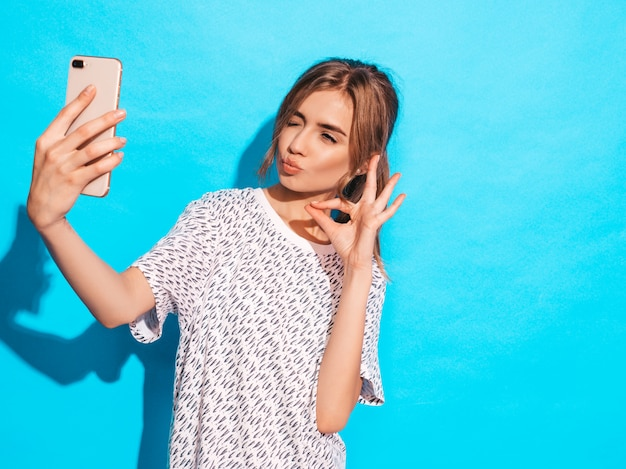 Portrait of cheerful young woman taking photo selfie. beautiful girl holding smartphone camera. smiling model posing near blue wall in studio. shows ok sign.winks and makes duck face Free Photo