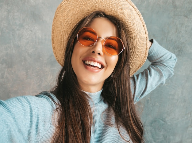 Portrait of cheerful young woman taking photo selfie and wearing modern clothes and hat. Free Photo
