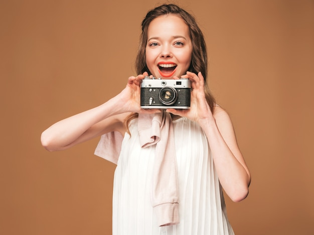 Portrait of cheerful young woman taking photo with inspiration and wearing white dress. girl holding retro camera. model posing Free Photo