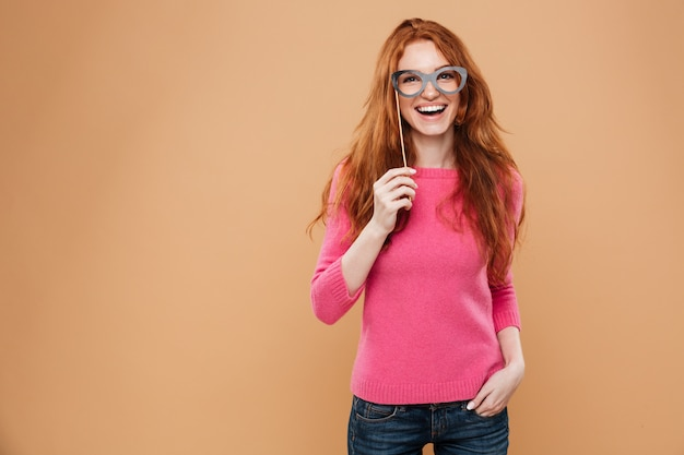 Portrait of a cheery young redhead girl with party glasses Free Photo