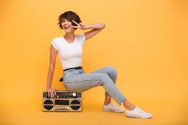 Portrait of a cheery young woman sitting record player Free Photo