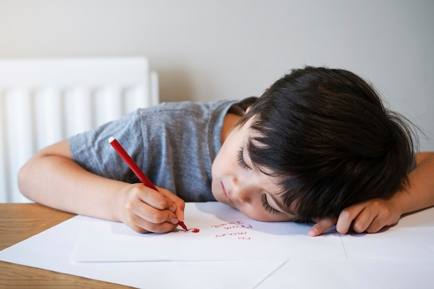 Portrait of child writing a letter, little boy drawing red heart on white paper for his mom. Premium Photo