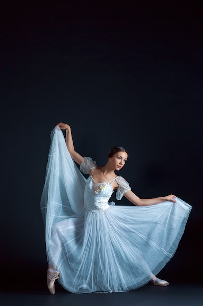 Portrait of the classical ballerina in white dress on black space Free Photo