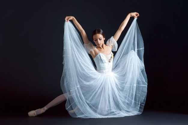 Portrait of classical ballerina in white dress on black Free Photo