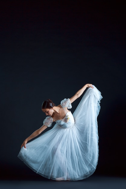 Portrait of classical ballerina in white dress on black Free Photo
