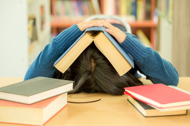 Portrait of clever student with open book reading it in college library Free Photo