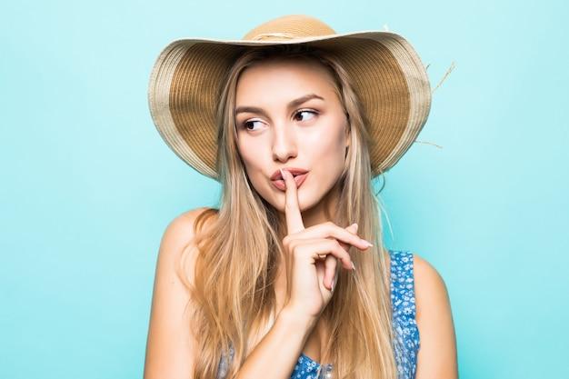 青い背景の上に秘密を隔離するために唇に指を示す大きな麦わら帽子を身に着けているヨーロッパの魅力的な女性の肖像画のクローズアップ 無料写真