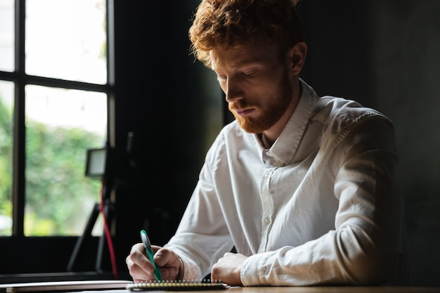 Portrait of a concentrated redhead man writing in a notebook Free Photo