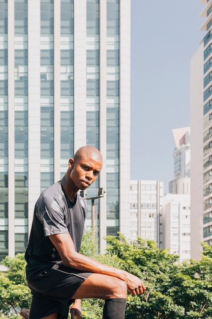 Portrait of a confidence athlete young man looking at camera standing against building Free Photo