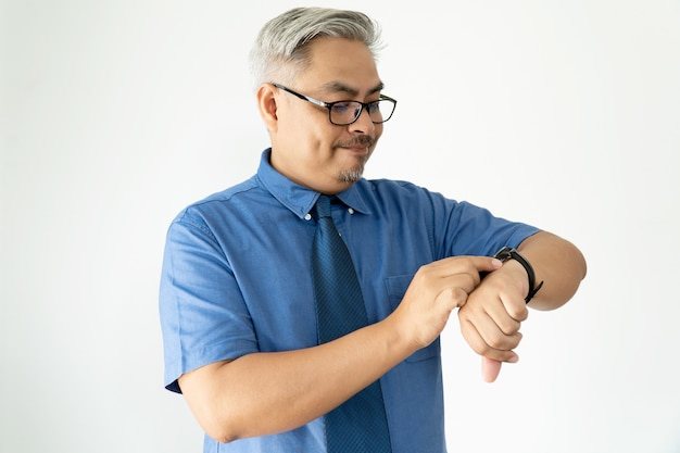 Portrait confident asian business man wearing glasses and short sleeve shirt looking at wristwatch on white Premium Photo