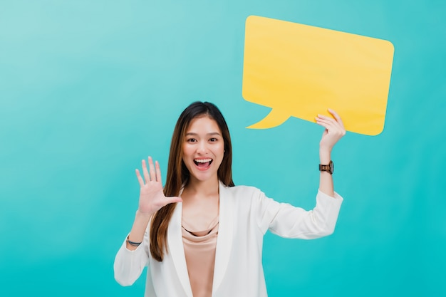 Portrait of confident beautiful asian business woman standing and holding blank yellow bubble speech. Premium Photo