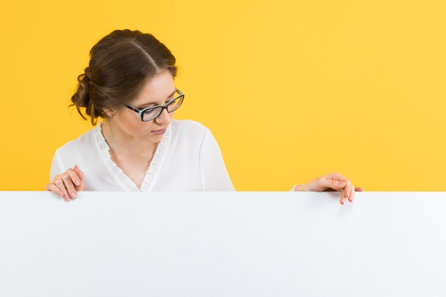 Portrait of confident beautiful happy smiling young business woman showing blank billboard on yellow background Premium Photo