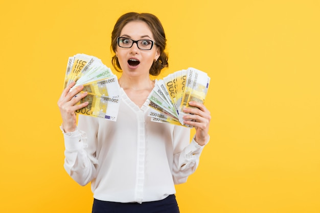 Portrait of confident beautiful happy young business woman with money in her hands standing Premium Photo
