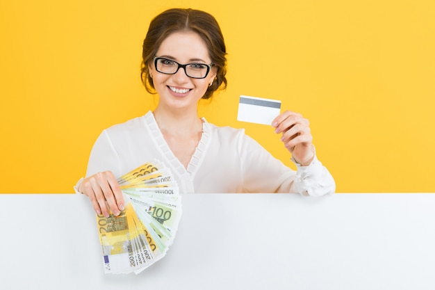 Portrait of confident beautiful young business woman with money and credit card in her hands with blank background Premium Photo