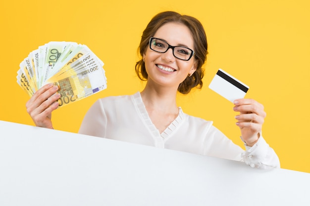 Portrait of confident beautiful young business woman with money and credit card in her hands Premium Photo