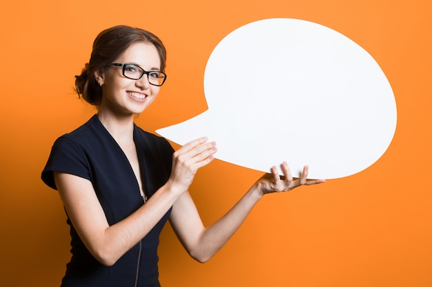 Portrait of confident beautiful young business woman with speech bubble in her hands standing on orange wall Premium Photo