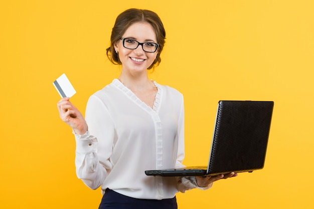 Portrait of confident beautiful young smiling business woman with laptop offering credit card on yellow Premium Photo