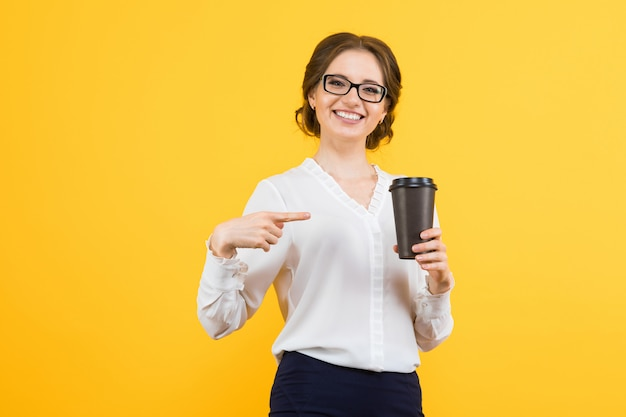 Portrait of confident beautiful young smiling happy business woman showing on cup of coffee with her hand on yellow Premium Photo