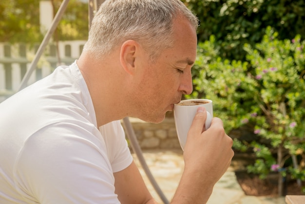 Portrait of a confident businessman sitting on the bench and drinking coffee outdoors. businessman drinking coffee in the garden. vintage tone. Free Photo