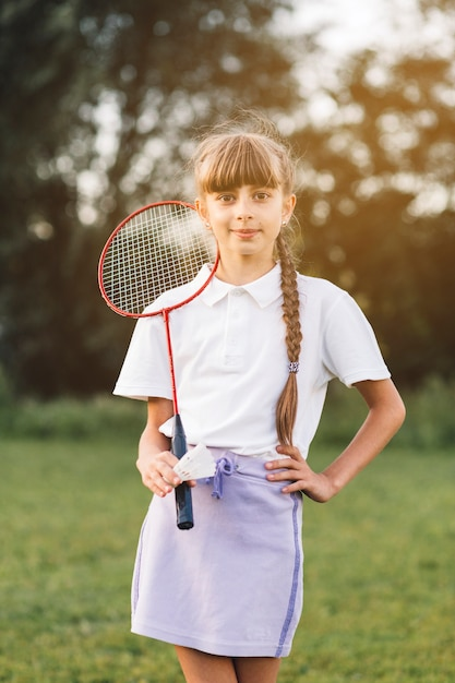 Portrait of a confident girl standing with badminton and shuttlecock Free Photo