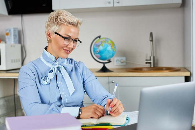 Portrait of confident good looking teacher sitting at table Premium Photo