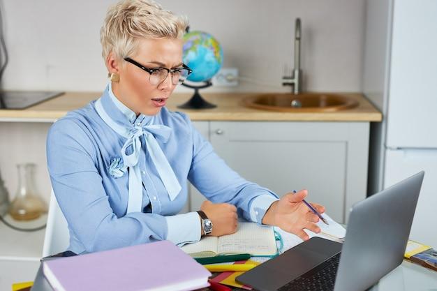 Portrait of confident good looking teacher sitting at table Premium Photo