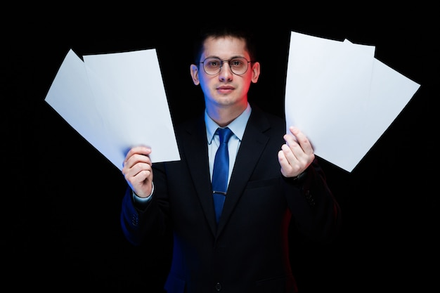 Portrait of confident handsome stylish businessman holding papers in his hands on black background Premium Photo