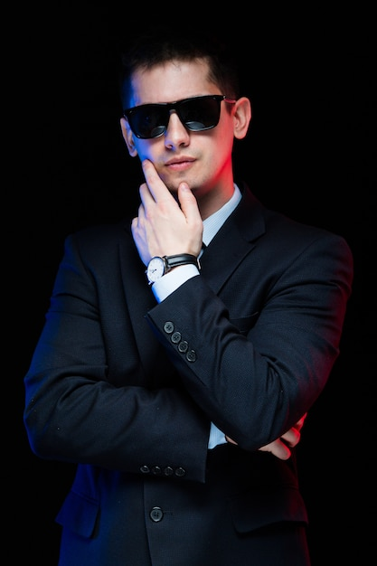 Portrait of confident handsome stylish businessman in sunglasses touching his chin on black Premium Photo