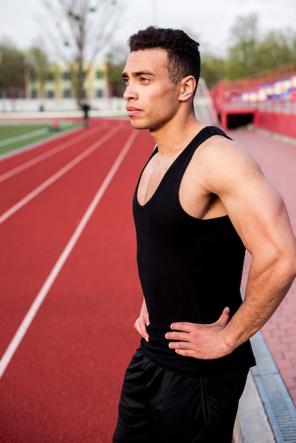 Portrait of a confident male athlete standing on running track Free Photo