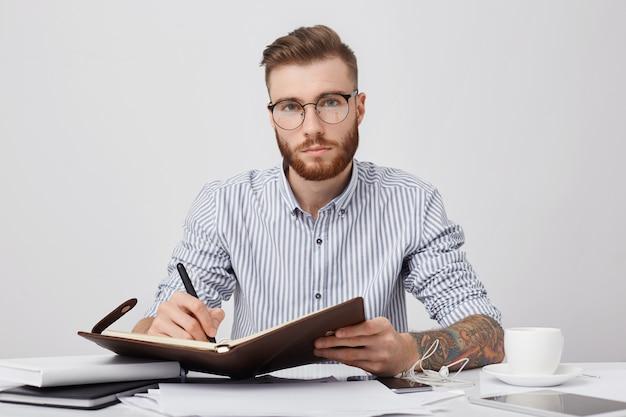 Ritratto di manager maschio fiducioso con tatuaggi, scrive nel piano di diario per la prossima settimana, beve caffè Foto Gratuite