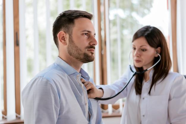 Portrait of confident practitioner checking heart beat of patient Premium Photo
