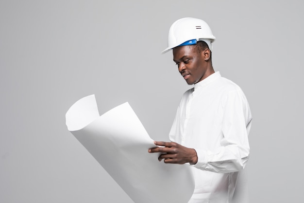 Portrait of confident, smiling afro american architect man with blueprint, looking at camera isolated on gray background Free Photo