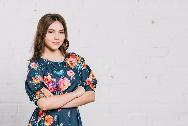 Portrait of a confident smiling teenage girl standing against wall Free Photo