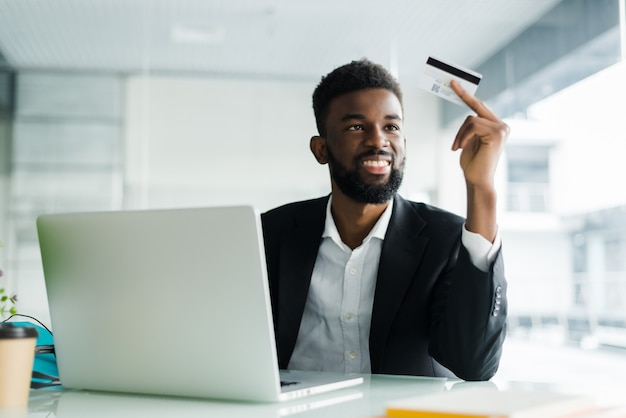 Portrait of confident young african man holding credit card with laptop paying via internet Free Photo