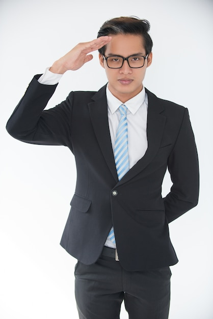 Portrait of confident young businessman saluting Free Photo