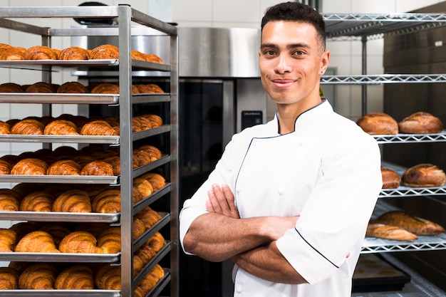 Portrait of a confident young male baker in front of baked croissant shelves Free Photo