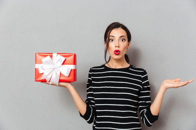 Portrait of a confused woman holding gift box Free Photo