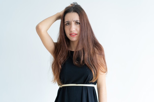 Portrait of confused young woman scratching head Free Photo