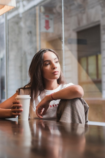 Portrait of a contemplated young woman holding disposable coffee cup in hand looking away Free Photo