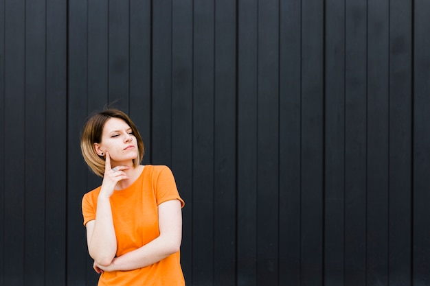 Portrait of a contemplated young woman standing against black wall Free Photo