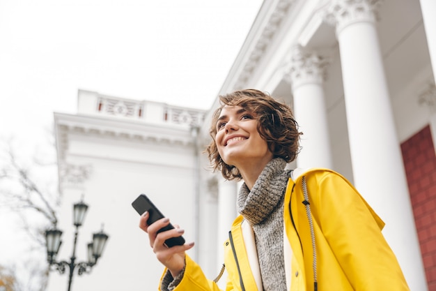 Portrait of content female 20s holding modern gadget receive text message on her smartphone while being outdoor Free Photo