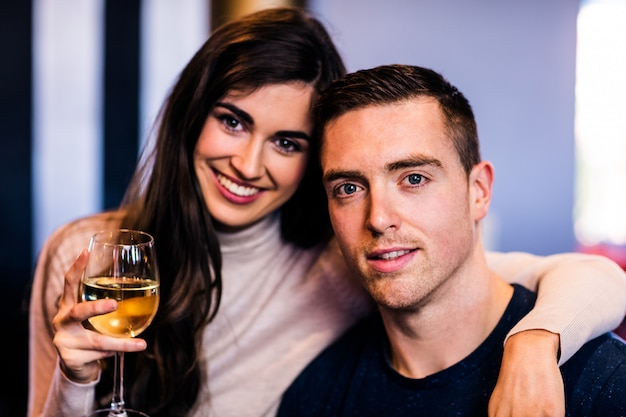 Portrait of couple holding glass of white wine and looking at the camera Premium Photo